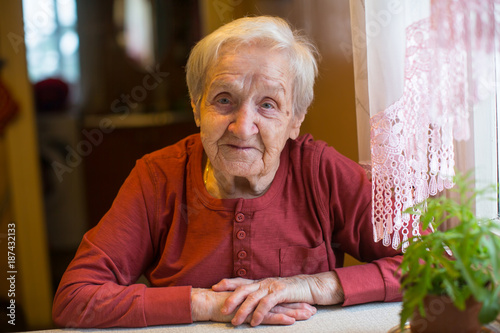 Foto Murales Portrait of an elderly woman sitting at table in the house.