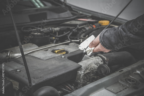 Man's hand using dipstick and checking oil level in car engine in the garage. Cares about car motor concept.