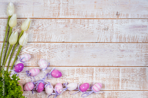 Colorful easter eggs and tulips over white wooden table - 187437388