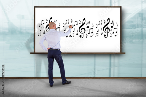 Businessman in front of a wall writing music notes - Art concept