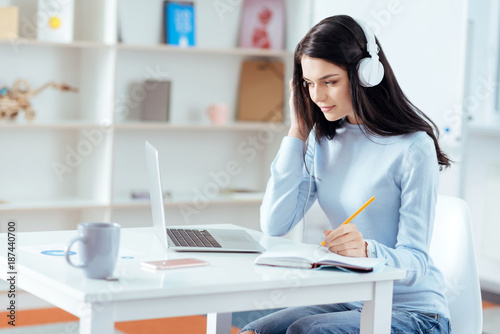 Music inspires. Pensive glad female student listening to music while looking at the screen and noting information