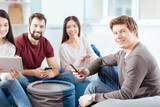 Cool company. Good looking young four friends relaxing while using  gadgets and smiling  - 187442551