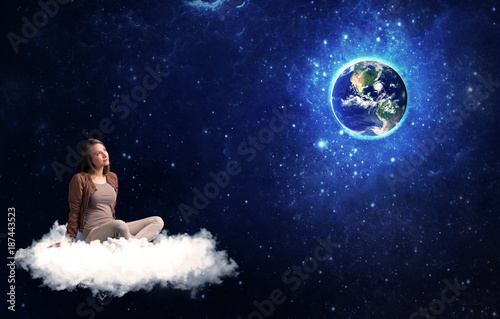 Woman sitting on cloud looking at planet earth - 187443523