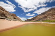 Panoramic view of rests of water during dry season near Ai-Ais Hot Springs at the base of the mountain peaks at the southern end of Fish River Canyon, in the Karas Region of southern Namibia, Africa.