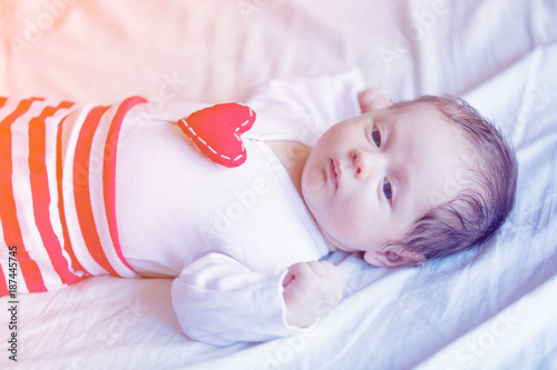 Little infant with heart shape toy on chest