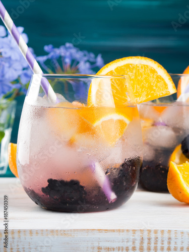 Foto Murales Alcohol Cocktail with blackberries and orange slices or infused detox water