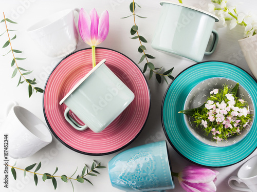 Foto Murales Spring tableware crockery concept with tulips flowers pastel color white background. Textured ceramic plates dishes mugs. Mother woman day gift idea