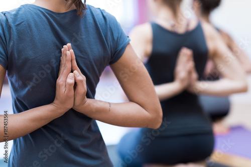 Fotobehang School de yoga Women practicing yoga: reverse prayer pose
