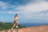 Athletic woman running up the mountain with sky and sea in background. Professional runner doing cardio work-out outdoor in natural landscape - 187455170