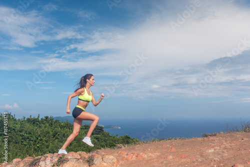 In de dag Jogging Athletic woman running up the mountain with sky and sea in background. Professional runner doing cardio work-out outdoor in natural landscape