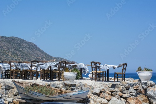 Many tables and chairs of the beautiful street restaurant on Crete in the sunny day near the sea