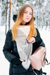 Attractive blond young adult woman walking through winter forest