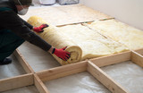 Work composed of mineral wool insulation in the floor, floor heating insulation , warm house, eco-friendly insulation, a builder at work - 187459322