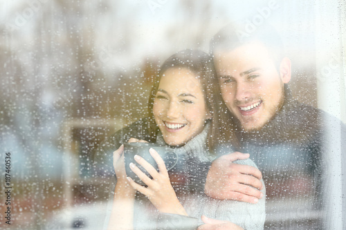 Positive couple looking through a window a rainy day