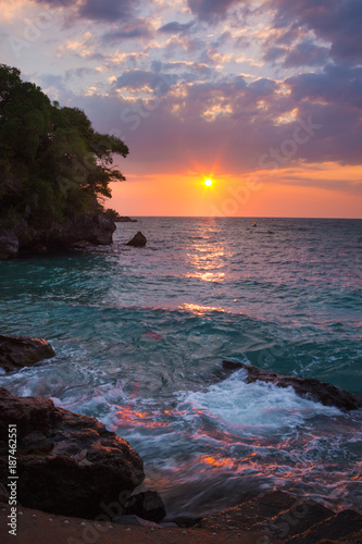 Foto op Canvas Zee zonsondergang View of coastline on Nosy Komba Island lined with palm trees and boats floating in the sea at sunset, Nosy Komba, Madagascar