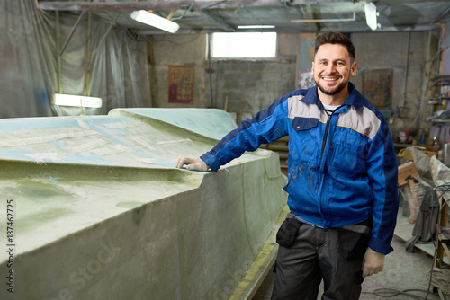 Portrait of modern mature man smiling happily at camera while posing in yacht workshop next to repaired boat , copy space
