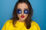 beautiful smiling woman with blue sunglasses and yellow blouse making a faces - 187463125