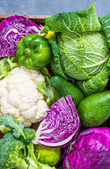 Variety of cabbages broccoli, savoy, cauliflower, violet cabbage, avocado, green peppers.