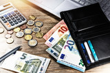 Euro banknotes and coins with wallet on work desk. Finances and budget
