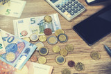 Euro banknotes and coins with smartphone on desk top. Online banking and finances