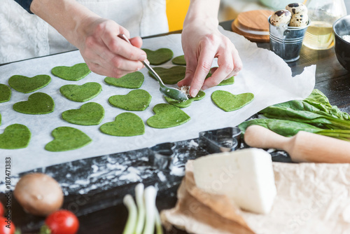 Poster Chef cook step by step makes green ravioli in the shape of a heart for a festive dinner