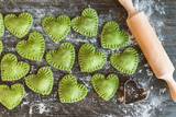 Green Ravioli in the shape of a heart on a wooden surface - 187472184