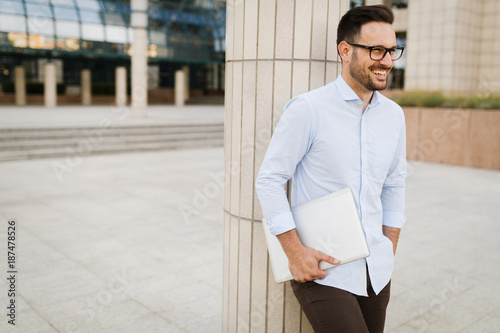 Businessman wearing glasses holding tablet