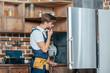 young repairman with tool belt looking at broken refrigerator