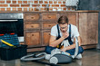 young repairman in protective glasses looking at broken vacuum cleaner
