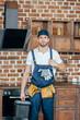 young repairman with toolbox showing thumb up and looking at camera