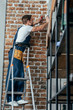 young electrician standing on ladder and working with plug