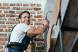 handsome young professional electrician smiling at camera