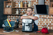 handsome young repairman leaning at coffee machine and smiling at camera