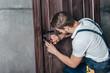 young repairman fixing door lock with screwdriver