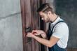 young worker repairing door lock with screwdriver