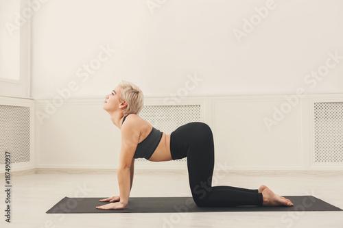 Foto Murales Young woman practicing yoga, Bitilasana exercise