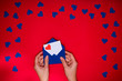 Woman's hands hold envelope with love letter above red background with many blue hearts around. Love concept