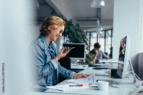 Businesswoman talking on smartphone and looking at documents