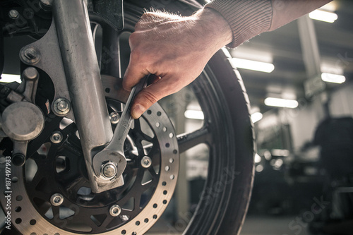 Close up of man's hand holding mounting wrench near the motorcycle's vehicle. Garage in back light on a background