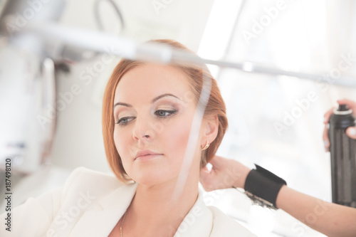 Aluminium Kapsalon Reflection of young woman in mirror and stylist doing hairstyle