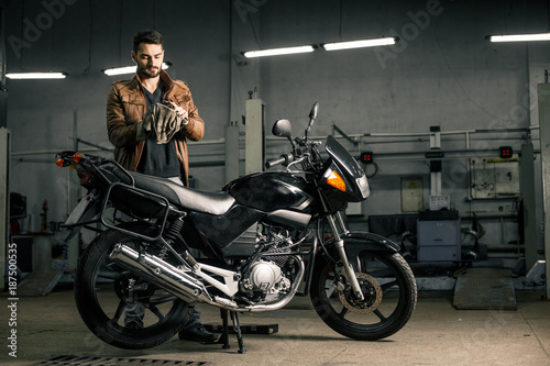 Young man in leather jacket standing near motorcycle in garage