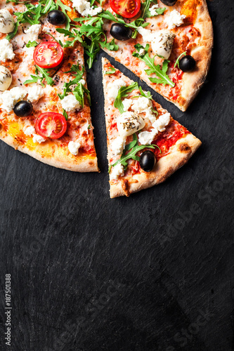 Hot pizza slice with melted mozzarella cheese and tomato on black concrete background.  Pizza Ready to Eat, Copyspace..
