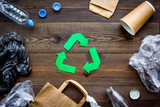 Green paper recycling sign among waste materials paper, plastic, polyethylene on dark wooden background top view - 187509352