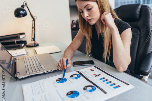 Female businesswoman readind financial report analyzing statistics pointing at pie chart working at her desk - 187514716