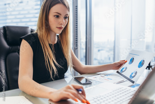 Foto Murales Female director working in office sitting at desk analyzing business statistics holding diagrams and charts using laptop
