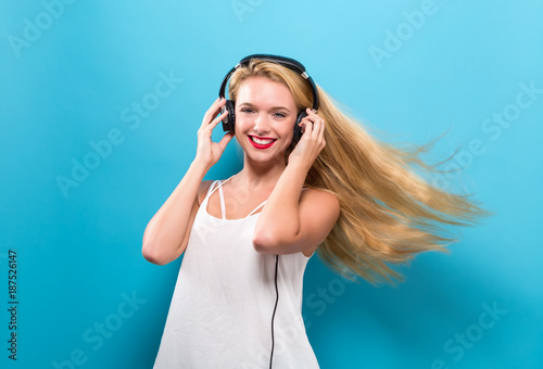 Happy young woman with headphones on a solid background - 187526147