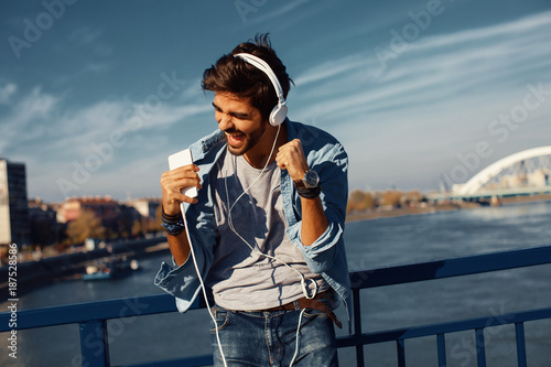 Young man listens to music via smartphone in the city