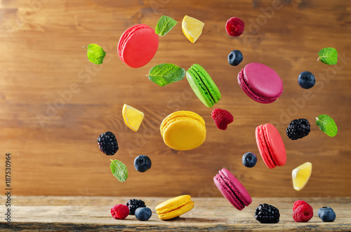 Poster Macarons Multicolored flying macaroni with berries and mint