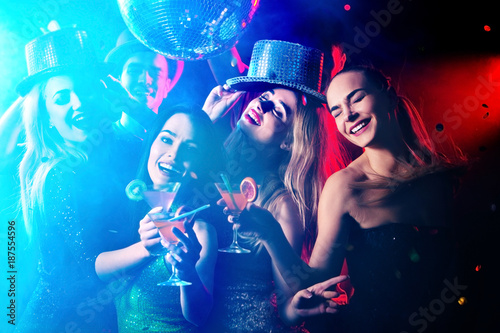 Foto Murales Dance party with group people . Dancing youth under influence of drugs. Women and confident casual smiling man have fun in night club. Seduce boozy woman cuddles up guy .