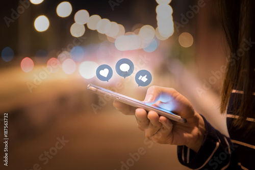 Leinwanddruck Bild Woman hands using mobile smartphone in the street with icon social media and social network.